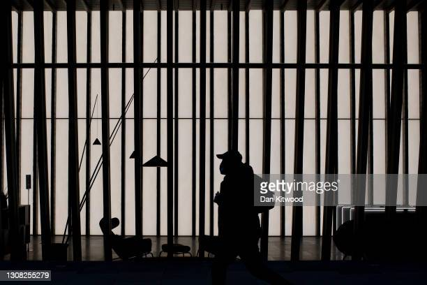 Member of the public walks past empty offices on March 17, 2021 in London, England. A year since the British government issued its first stay-at-home...