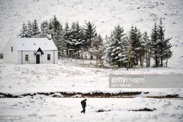Member of the public walks past Lagangarbh cottage below Buachaille Etive Mor on February 1, 2019 in Glen Coe Scotland. The Met office have yellow be...