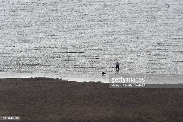 Member of the public walks their dog on a nearby beach during the second round of The 143rd Open Championship at Royal Liverpool on July 18, 2014 in...