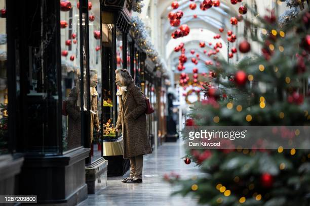 Member of the public walks through Burlington Arcade decorated with Christmas Trees on November 23, 2020 in London, England. UK Prime Minister, Boris...
