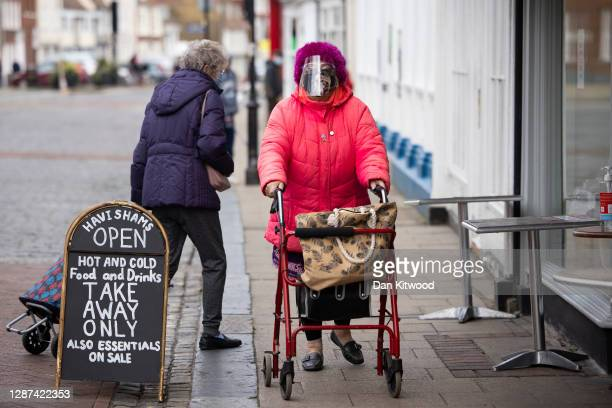 Member of the public wearing a face visor walks down the high street on November 24, 2020 in Faversham, Kent. The Swale Valley borough in Kent,...