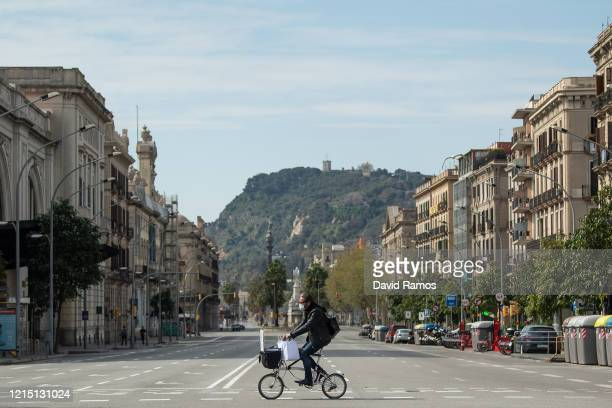 A member of the public wearing a protective face mask rides his bike on an empty street on March 27 2020 in Barcelona Spain Spain plans to continue...
