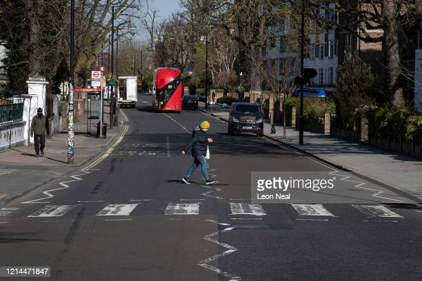 A member of the public wearing a protective mask carries her shopping as she crosses the road near to the iconic Abbey Road pedestrian crossing on...