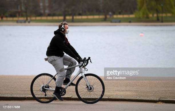 A member of the public wearing a protective mask cycles in Hyde Park on March 29 2020 in London England The coronavirus pandemic has spread to at...