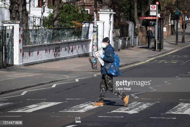 A member of the public wearing a protective mask holds a newspaper with a Covid19 headline as he walks on the iconic Abbey Road pedestrian crossing...