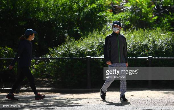 A member of the public wearing a protective mask looks on April 26 2020 in LondonEngland The British government has extended the lockdown...