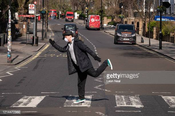 A member of the public wearing a protective mask poses as he walks on the iconic Abbey Road pedestrian crossing on March 24 2020 in London England...