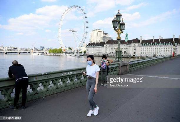 A member of the public wearing a protective mask walks across Westminster Bridge on May 07 2020 in London England The UK is continuing with...