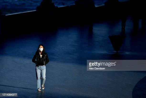 A member of the public wearing a protective mask walks along the embankment on March 22 2020 in London England Coronavirus has spread to at least 188...