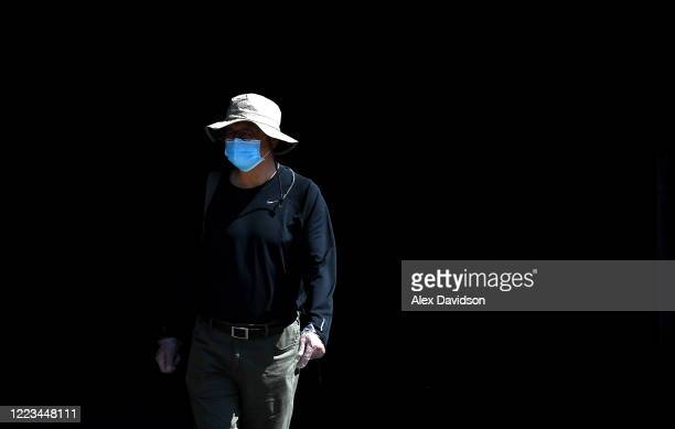 A member of the public wearing a protective mask walks down the South Bank on May 07 2020 in London England The UK is continuing with quarantine...