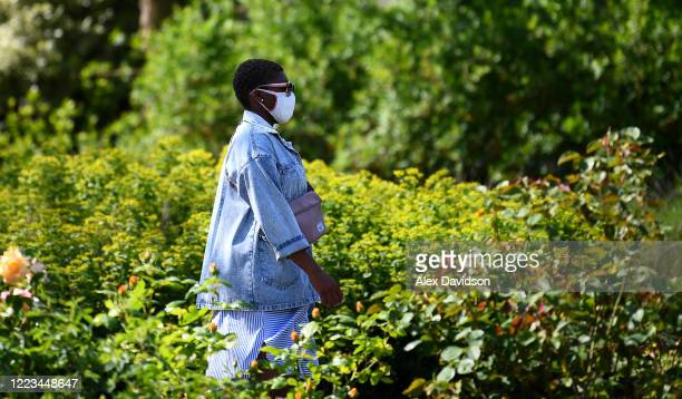 A member of the public wearing a protective mask walks through The Imperial War Museum Gardens on May 07 2020 in London England The UK is continuing...