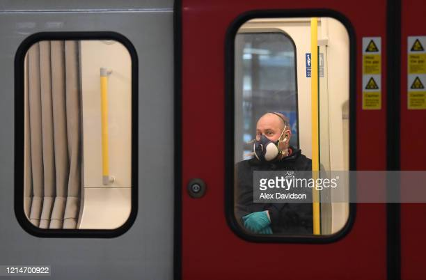 A member of the public wears a a protective mask on the Tube on March 25 2020 in London England British Prime Minister Boris Johnson announced strict...