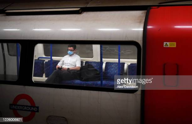 A member of the public wears a protective mask on a tube on May 20 2020 in London England The British government has started easing the lockdown it...