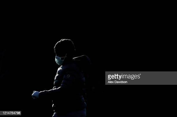 A member of the public wears a protective mask whilst walking round St James's Park on March 25 2020 in London England British Prime Minister Boris...