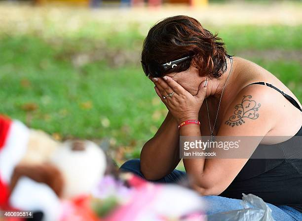 Member of the public weeps at the scene of a memorial which is located in the park next the home of a multiple stabbing in the suburb of Manoora on...