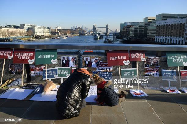 TOPSHOT A member of the public writes condolences on London Bridge in memory of the victims of last weeks attack in central London on December 12...