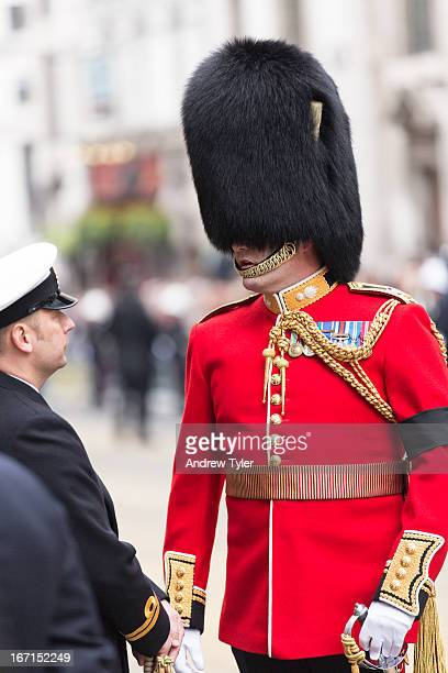 Member of the Queen's Guard chatting to another member of the military despite appearing to have his eyes covered by his headwear.