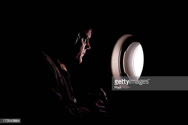 A member of the RAF flight crew looks out through a window of the C17 Globemaster transport plane as it comes into land at Atyrau airport on July 1...