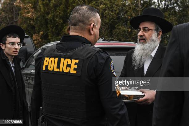 A member of the Ramapo police stands guard in front of the house of Rabbi Chaim Rottenberg on December 29 2019 in Monsey New York Five people were...