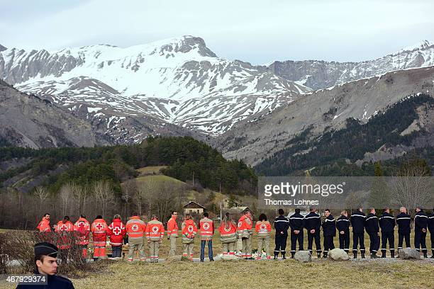 Member of the Red Cross and Policemen waite for relatives at a monument to honour the victims of Germanwings flight 4U9525 in front of the mountains...