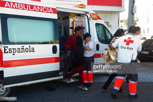 A member of the Red Cross helps a pregnant woman to get off an ambulance in Tarifa on August 10 after she was rescued along with six wouldbe...