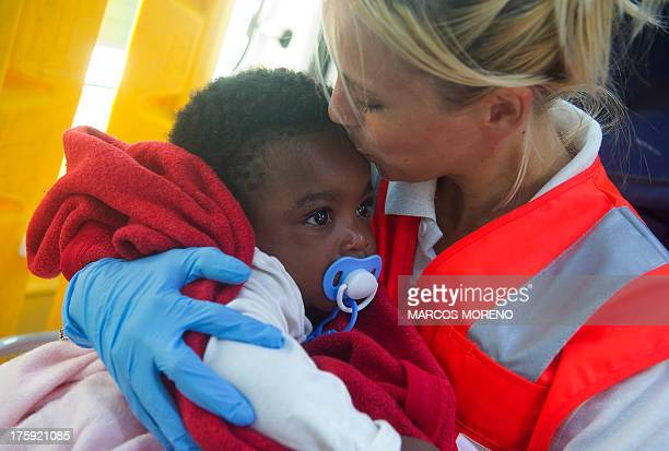 A member of the Red Cross kisses the forehead of a baby at Tarifa's harbour on August 10 after 86 wouldbe immigrants were rescued across the Straight...