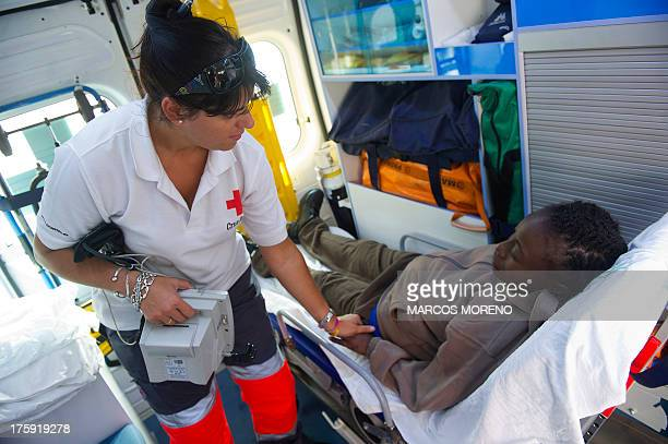 A member of the Red Cross tends to a wouldbe immigrant in an ambulance at Tarifa's harbour on August 10 after 86 wouldbe immigrants were rescued off...