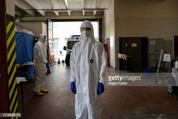 A member of the Red Cross wears a protective suit after transporting a coronavirus patient during the nationwide lockdown on April 18 2020 in Turin...