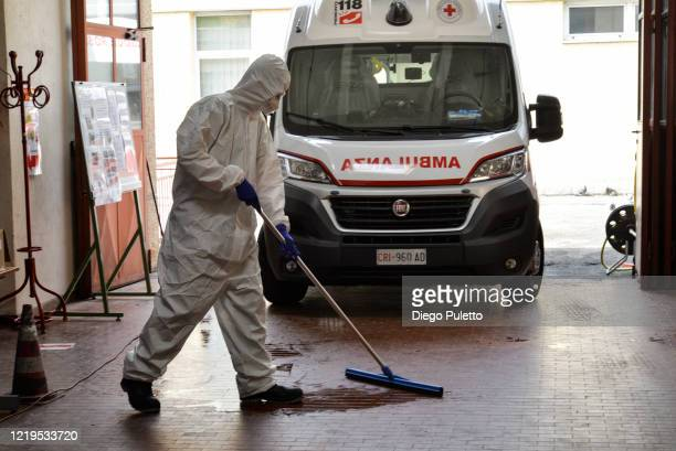 A member of the Red Cross wears a protective suit and sanitises the floor after transporting a coronavirus patient during the nationwide lockdown on...