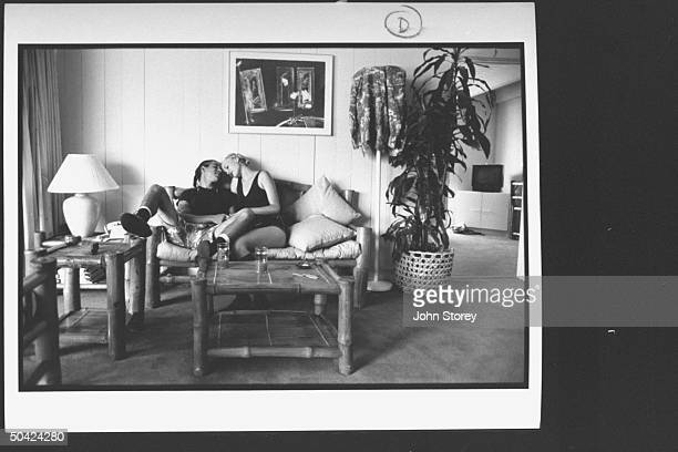 Member of the Red Hot Chili Peppers band Anthony Kiedis relaxing in room decorated w bamboo furniture snuggling on couch w girlfriend Carmen Hoff at...