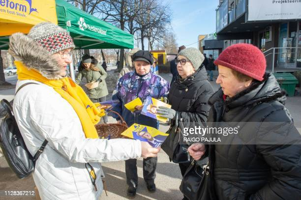 A member of the Reform party hands over leaflets on March 2 2019 in Tallinn on the eve of Estonia's general elections