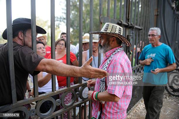 Member of the regional parliament for the United Left party in Andalucia Juan Manuel Sanchez Gordillo speaks to an activisit through the gates of a...