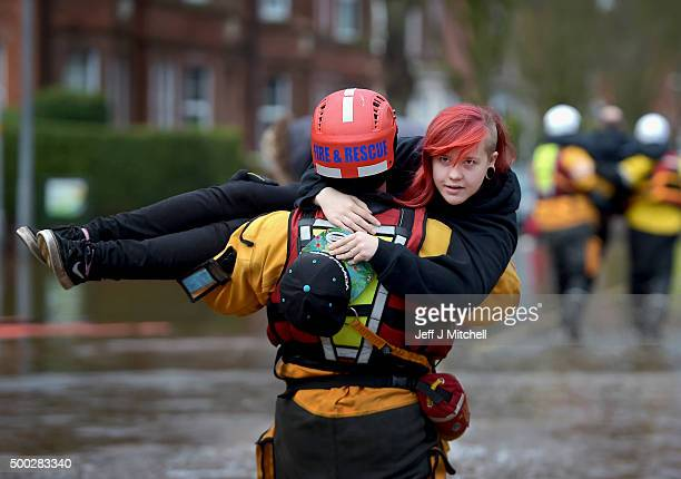 A member of the rescue team carries a young woman to safety through the flood water as they continue to to evacuate homes after Storm Desmond caused...