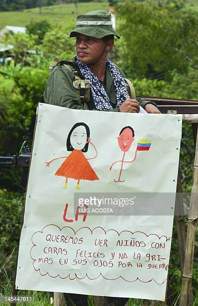 A member of the Revolutionary Armed Forces of Colombia stands behind a poster reading 'We Want Children With Happy Faces And Not With Tears In Their...