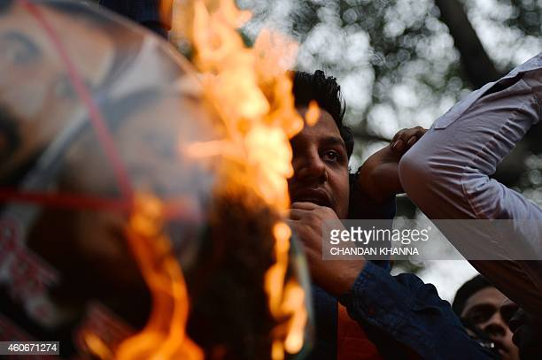 A member of the rightwing Hindu Sena burns a poster bearing images of Pakistani Prime Minister Nawaz Sharif and Hafiz Muhammad Saeed and ZakiurRehman...