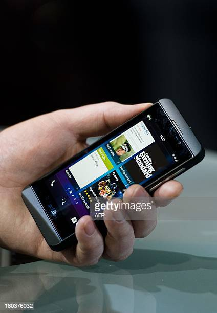 A member of the RIM team poses with one of the new touchscreen Z10 Blackberry devices in central London at one of eight simultaneous worldwide events...