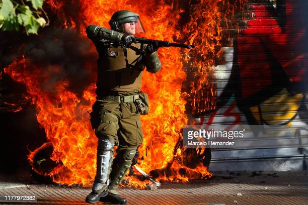 A member of the riot police gets ready to repel the attacks of protesters during a protest against President Sebastian Piñera during the seventh day...