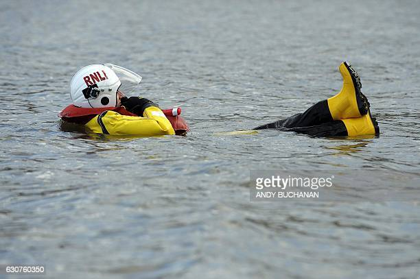 A member of the RNLI lifeguards floats as participant take part in the annual New Year's Day 'Loony Dook' swim in the Firth of Forth in South...