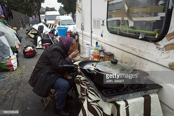 A member of the Roma community eats at a camp on October 18 in IvrysurSeine in the suburbs of Paris AFP PHOTO / JOEL SAGET