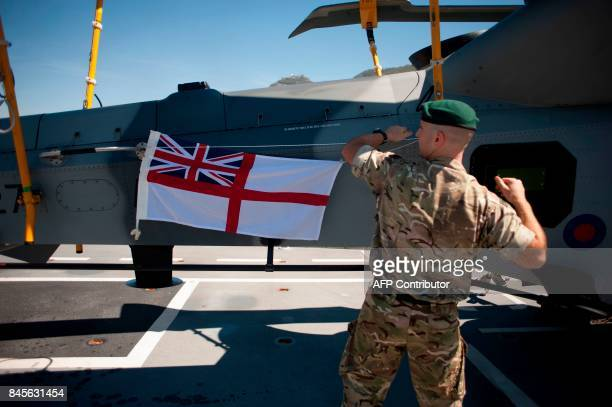 A member of the Royal Air Force hangs a British Navy White Ensign on an helicopter on board the amphibious assault ship HMS Ocean at the Naval Base...