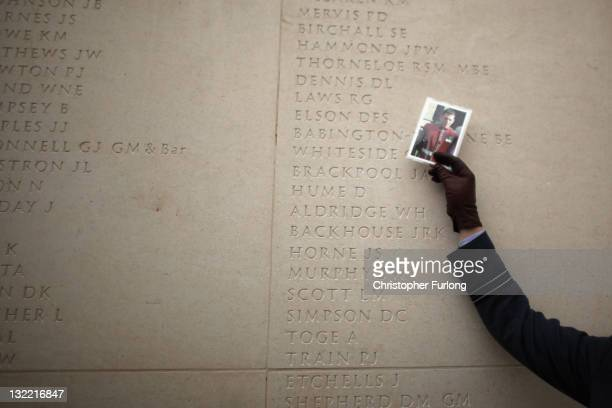 Member of the Royal Air Force holds up a photograph of a comrade next to the names of the fallen at the National Memorial Arboretum on Armstice day...