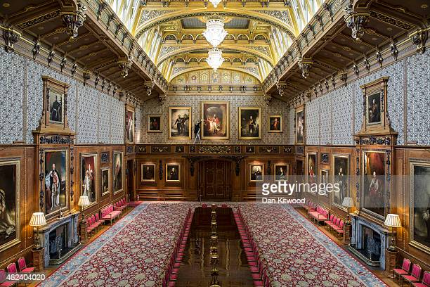 A member of the Royal Collection staff poses besides a portrait of the Duke of Wellington in the Waterloo Chamber during a press preview for Waterloo...