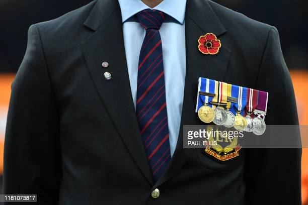 A member of the Royal Military Police wearing service medals pays his respects ahead of Remembrance Day during the English Premier League football...
