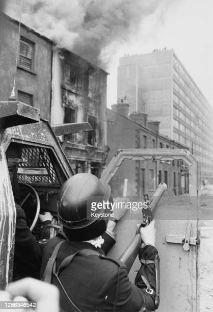 Member of the Royal Ulster Constabulary takes shelter behind the door of an armoured vehicle as violence flared between local residents, organised...