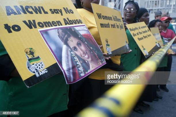 A member of the ruling African National Congress Women's League holds a picture of Anni Dewani during a protest against violence against women...