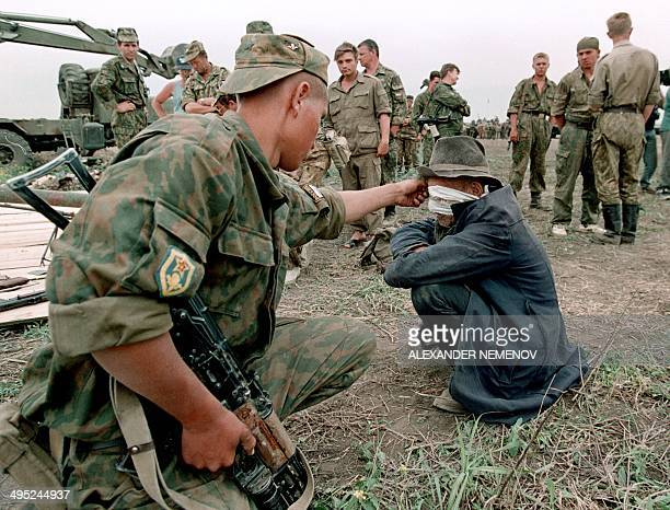 A member of the Russian Army 'special forces' surrounded by fellow officers interrogates a blindfolded Chechen prisoner in May 1996 in the Chechen...