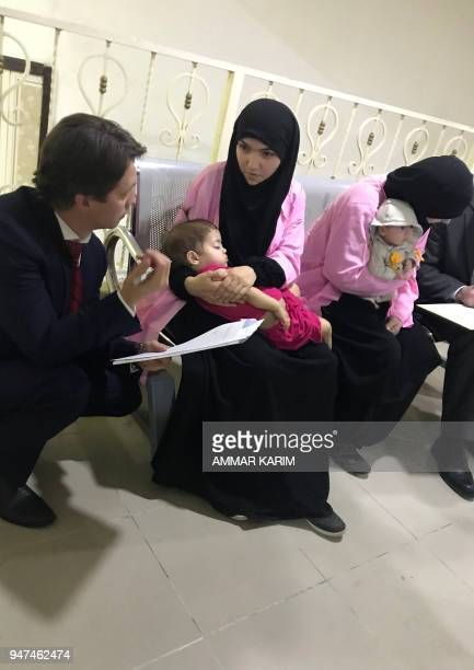 A member of the Russian diplomatic corps talks with two Russian nationals as they attend their trial at the Central penal Court in Baghdad on April...