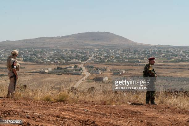 A member of the Russian military police and a member of the Syrian government forces patrol in the Syrian Golan Heights on August 14 2018