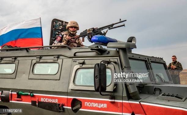 Member of the Russian military police mans a turret in an armoured vehicle during a patrol along the Syria-Turkey border by the town of Darbasiyah in...