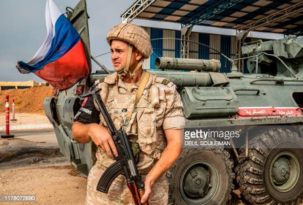 A member of the Russian military police stands outside an armoured personnel carrier at a position along the SyriaTurkey border by the town of...